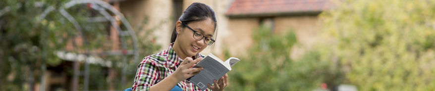 UWA student reading in campus grounds