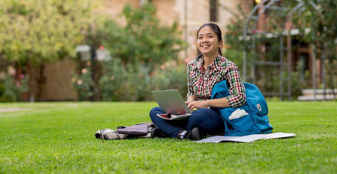 Student studies outdoors on the UWA campus