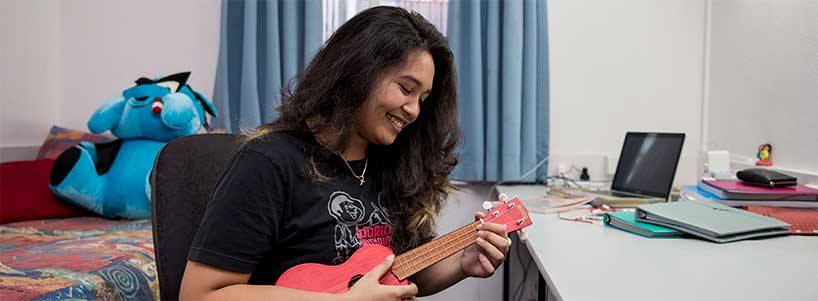 Student plays the ukelele in her room