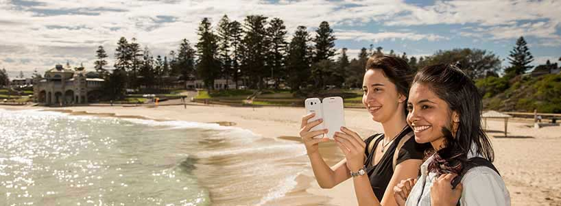 Students take photos of golden sandy Perth beach
