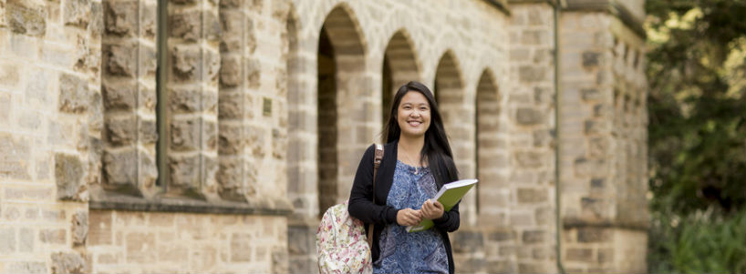 Happy UWA student in front of sandstone buildings
